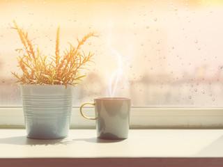 Steamong coffee cup on wood table with rain drop window backgrou