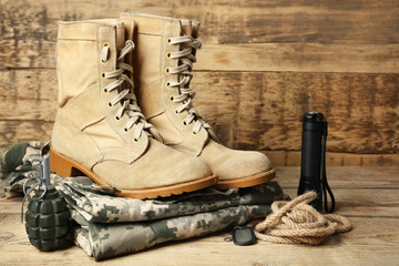 Set of military outfit on wooden background, close up Wall mural