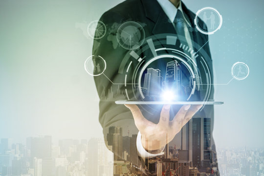double exposure of  smart city and a business person holding tablet pc