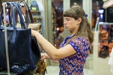 Young woman choosing a bag at shop