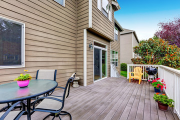 Wooden walkout deck with backyard view.