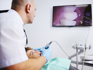Male dentist examines a patient in the dental chair. Dentist patient shows his teeth on the big screen
