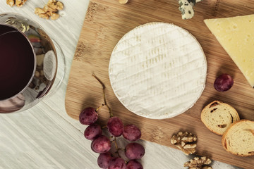 Round of Camembert cheese with wine and copyspace