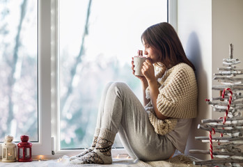 Young beautiful woman drinking hot coffee sitting on window sill