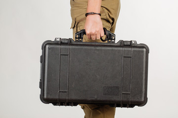 guard hand in handcuffs close up holding case with money