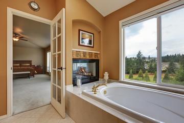 Luxury bathroom interior. Wall mounted fireplace with bath tub