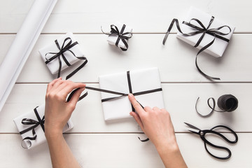 Woman's hands give wrapped christmas holiday handmade present in white paper with black ribbon. Present, box, decoration of gift on white wooden table, top view with copy space.