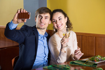 Positive young spouses sitting at restaurant table with smartpho