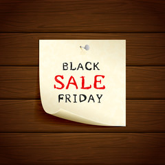 Paper with Black Friday Sale on wooden background