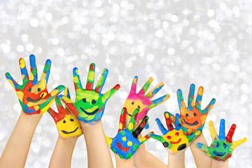 angemalte Kinderhände vor weihnachtlichem Hintergrund