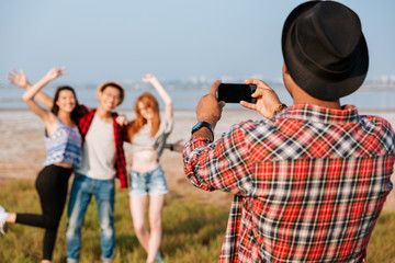 Man taking pictures of friends with blank screen cell phone