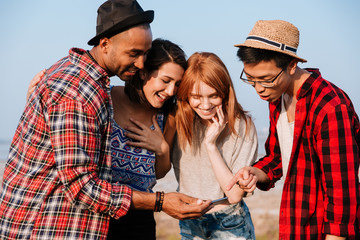 Smiling young people standing and using smartphone together