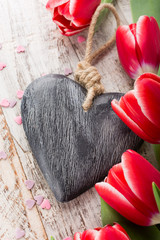Valentines Day background with decorative heart and pink tulips on white old wooden planks with copy space for text. Valentine's Day concept. View from above.