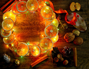 Christmas hand made craft template evening light background. Make traditional New Year`s door wreath components: tree cones, dried oranges, cinnamon, ribbon and colorful garland lights. Copyspace.
