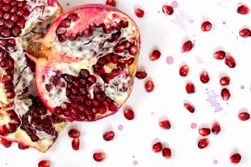 Pomegranate fruit and seeds on white background