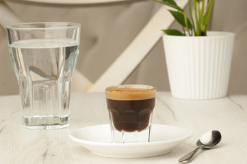 empty glass and a cup of coffee with a spoon on a white table with a flower