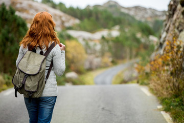Woman traveler with a backpack on his shoulders walking along the road. The road through the rocks. Scandinavia, autumn, cloudy.