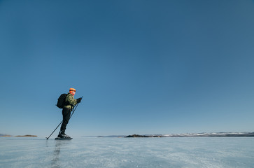 Tourists travel to Norway hiking ice skating on the frozen lake. Special long skate for long distances. Mounting under the ski boots. Location of Lake Baikal action. The Russian called Bayes or Loft.