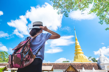 Woman traveler with temple background in thailand