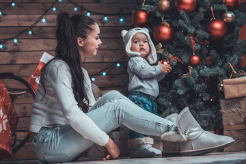 Young mother and her baby decoraring xmas tree