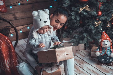 Young mother and her child holding xmas gifts