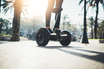 Young hipster girl driving on hoverboard at sunny park, active woman balancing on modern electric segway, alternative transport concept, ecology and environment concept, flare light