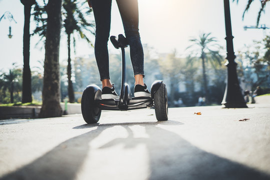 Back view of young hipster girl balancing on electric hoverboard at the sunny park, active woman using and driving on segway outdoor, film effects, flare light