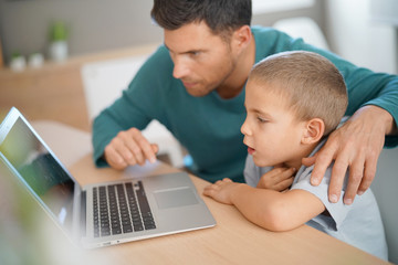 Daddy with kid using laptop computer for e-learning