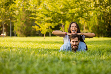 smiling woman lying on her lover outside in grass