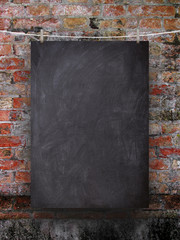 Single blank black blackboard frame hanged by clips against red weathered brick wall background
