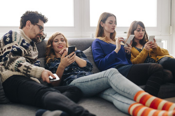 Four friends with smartphones on couch in living room hanging out