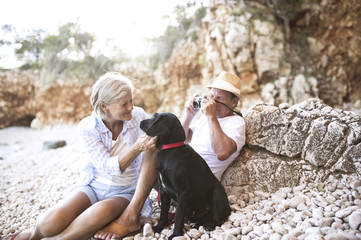 Senior couple relaxing with dog on the beach