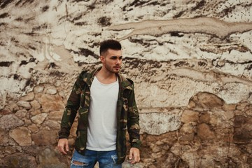 Attractive guy with jacket military stylish on a wall of mud