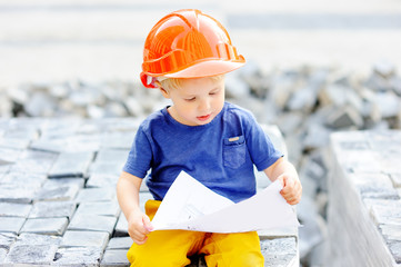 Portrait of little builder in hardhats reading construction drawing