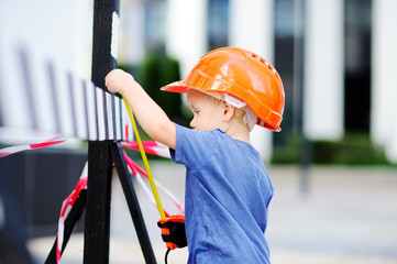 Portrait of cute little builder in hardhats with ruler working outdoors