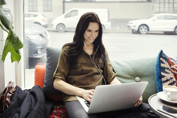Smiling businesswoman using laptop while sitting on sofa against window