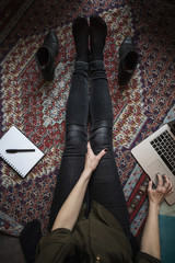 Low section of blogger using laptop while sitting on carpet