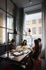 Creative business team sitting at table working in modern office
