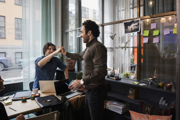 Happy businessmen high-fiving in creative office