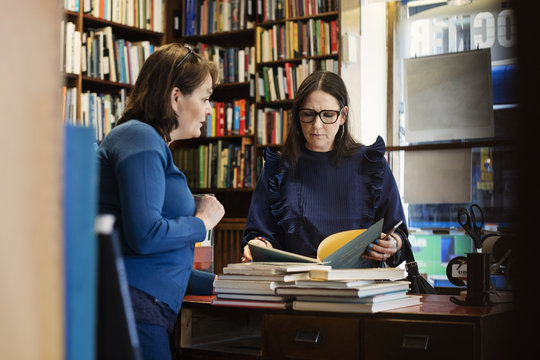 Female customer discussing with librarian standing in bookstore