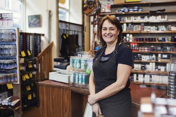 Portrait of happy shoemaker standing in shop