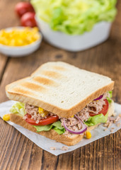Wooden table with a Tuna Sandwich (selective focus)
