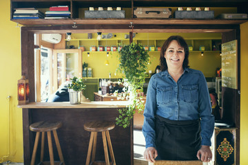 Portrait of happy owner standing in coffee shop