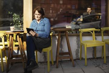 Female owner using digital tablet while sitting at sidewalk cafe