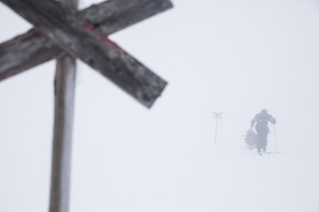 Distant image of man skiing with cross sign in foreground