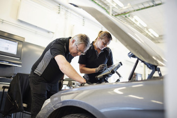 Male and female technicians examining car at shop