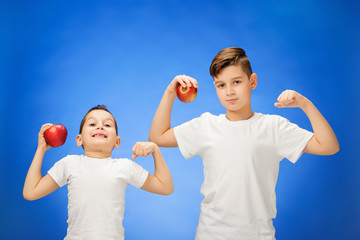 Handsome little boys with two red apples. Studio portrait over blue background