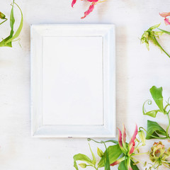 White photo frame with orchids and gift boxes on the vintage table. Anniversary, wedding, happy birthday background Greeting card template. Holiday mock-up.