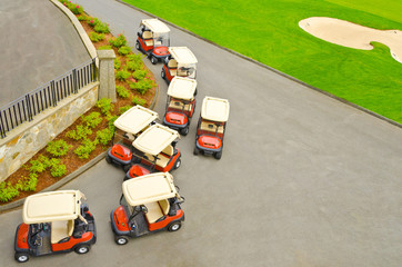 A bunch of golf carts over green and bunker.