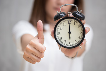 Good job, Best to do in time or great times concept, women show  thumb up hand hold retro clock show at 6 o'clock.